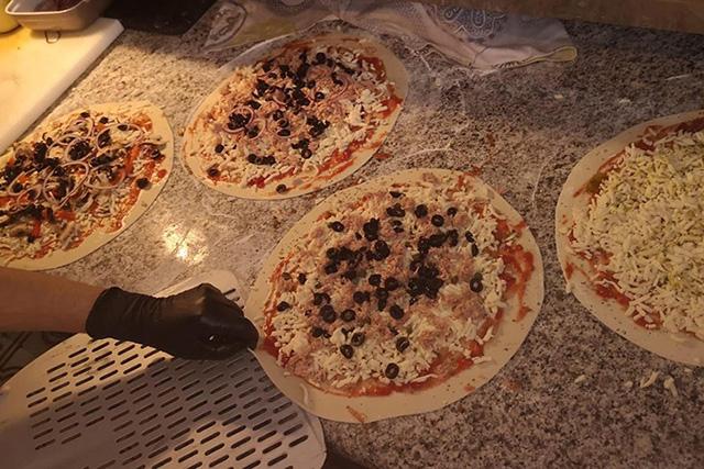 Imagen de varias pizzas en preparación